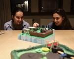 Elvebakkenelevene, og frokostseminarets konferansierer, Jennifer og Lea ser på en av modellene elevene på Hovseter  har laget.